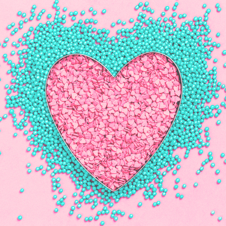 Pink and mint colors cake sprinkles sweets heart shape on pink background with copy space, flat lay. Love, Mothers and Valentines Day and charity concept