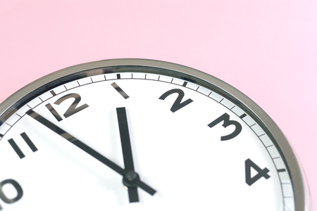 Part of analogue plain wall clock on trendy feminine pink background. Close up with copy space, time management concept and lunch time