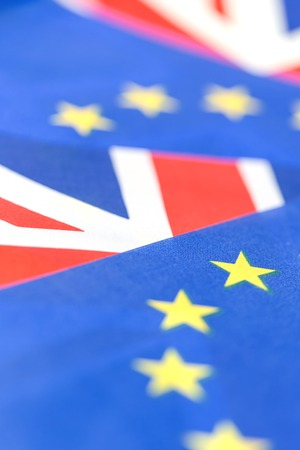 Background of EU and UK waving flags, part of Union Jack visible with copy space. Brexit and cooperation concept
