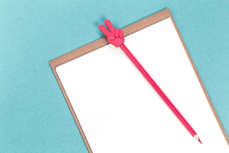 A red pencil with V sign and a blank notepad on blue background. Flat lay with copy space Stock Photo