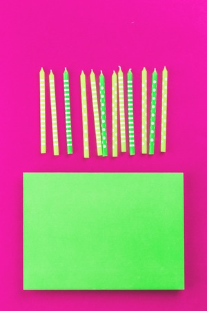 Bright festive green candles in a row on trendy fucsia neon plastic pink background in flat lay with copy space. Greeting happy birthday feminine girlie celebration card or party invitation