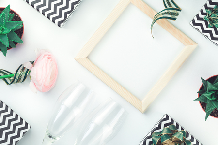 Black and white chevron gift boxes with green bows frame isolated on white with flower sparkling wine glasses. Christmas, Valentine, thanksgiving celebration, black friday, shopping or blogger background Stock Photo