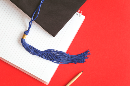 Black Graduation Cap with notebook on red background. 写真素材