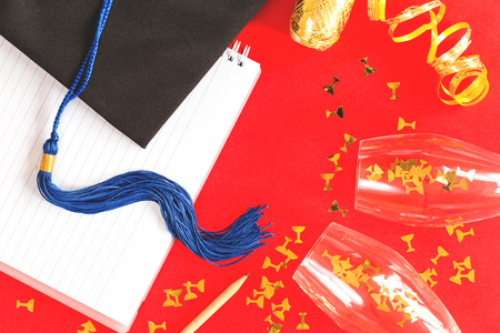 Black Graduation Cap with notebook on red background. University or college graduation celebration with golden ribbon and glasses. 写真素材