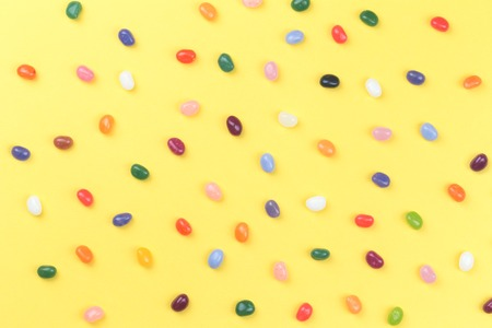 Colorful assorted jelly bean sweets on bright yellow background in flat lay with copy space. Party or celebration backdrop
