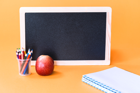 Red apple with pencils and school black board and a notebook on orange background. Back to school and knowledge skills with education concept with copy space