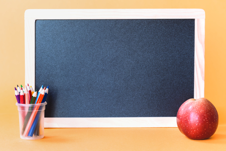 Red apple with pencils and school black board on orange background. Back to school and knowledge skills with education concept with copy space