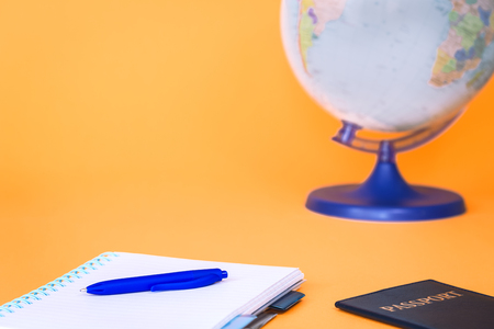 Passport, globe and notebook on orange background. Travel route and vacation planning concept with copy space Foto de archivo