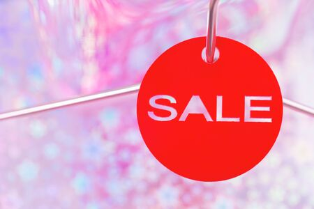 Red shopping sale tag on festive purple pink trendy holographic background and metal coat hanger with copy space