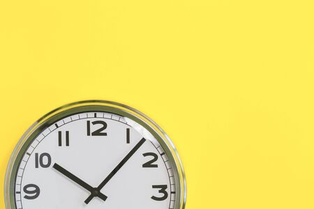 Part of analogue plain wall clock on trendy yellow background. Ten o'clock. Close up with copy space, time management or school concept and lunch time