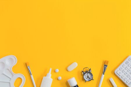 Assorted office and school white stationery on bright yellow background with alarm clock. Flat lay with copy space for back to school or education and craft concept