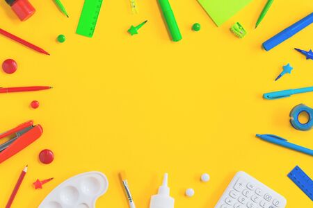 Assorted office and school red green blue and white stationery on bright yellow background. Flat lay with copy space for back to school or education and craft concept. Border or frame