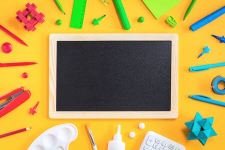 Assorted office and school red green blue and white stationery on bright yellow background with black board. Flat lay copy space for back to school or education development and craft concept. frame