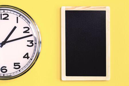 Teil der analogen einfachen Wanduhr und des schwarzen Anschlagbretts auf trendigem gelbem Hintergrund. Ein Uhr. Nahaufnahme mit Kopierraum, Zeitmanagement oder Schulkonzept und Mittagsöffnungszeiten Standard-Bild