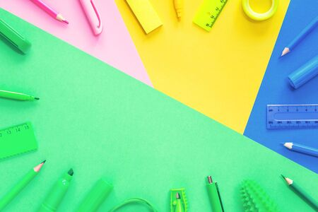 Assorted office and school pink green blue and yellow stationery on bright color blocks background. Flat lay with copy space for back to school or education and craft concept. Border or frame