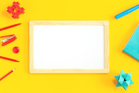 Assorted office and school red and blue stationery on bright yellow background with white board. Flat lay with copy space for back to school or education development and craft concept. Border or frame