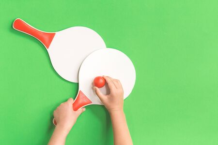 Hands holding one of two white and red beach tennis paddle racket with red tennis table ball against green background. Flat lay with copy space. Outdoors summer activity, education break kids fun