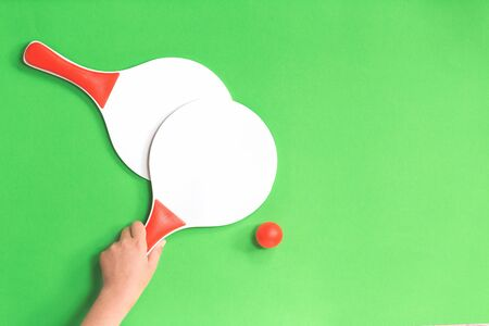 Hand holding one of two white and red beach tennis paddle racket with red tennis table ball against green background. Flat lay with copy space. Outdoors summer activity, education break kids fun