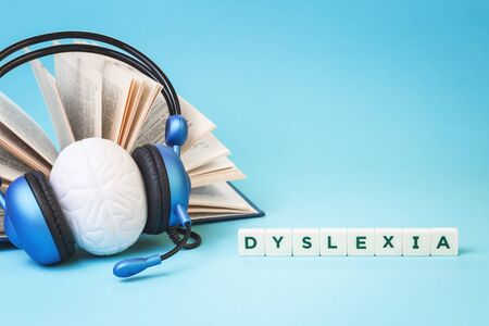 Dyslexia word with an open book and brain stress relief in headphones on blue background, reading difficulty and disorder and auditory memory concept. Education and neurology with copy space
