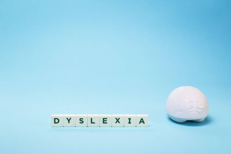 Dyslexia word with a brain stress relief on blue background, reading difficulty and disorder visual and auditory memory or test concept. Education and neurology with copy space