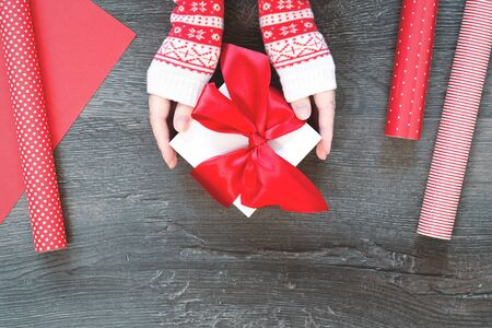 Hands in Christmas sweater hold red ribbon bow gift box on wooden background with red striped polka dot gift wrapping paper. New Year season greetings card resolutions or goals. flat lay copy space