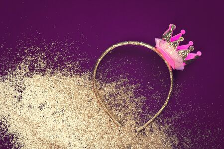Pink and gold princess crown headband for girls on dark purple background with golden dust glitter. Festive birthday party or performance with copy space Stockfoto