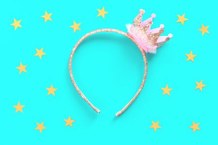 Pink and golden glitter princess crown headband for girls on blue background. Festive birthday party or performance. Flat lay with copy space