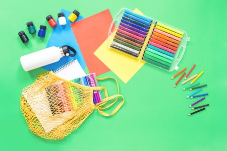 Assorted office or school sets of multicolored rainbow stationery on pastel green background with crochet net eco bag. Flat lay copy space. back to school or creative education craft design concept.