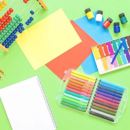 Assorted office or school sets of multicolored rainbow stationery on pastel green background. Flat lay with copy space. back to school or creative education craft design concept.