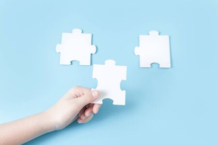 Jigsaw puzzle piece in a hand. Teamwork and solution or idea concept with copy space on trendy pastel blue background