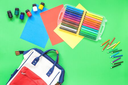 Assorted office or school sets of multicolored rainbow stationery school bag backpack, water bottle on green background. Flat lay copy space. back to school or creative design education craft concept.