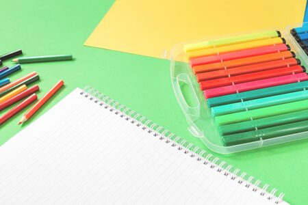 Assorted office or school sets of multicolored rainbow stationery on pastel green background and white notepad. Flat lay with copy space. back to school or creative education craft design concept.