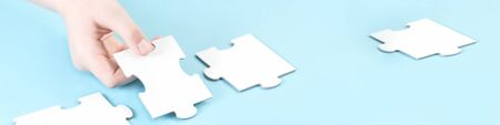 Jigsaw puzzle piece in a hand. Teamwork and solution or idea concept with copy space on trendy pastel blue background banner