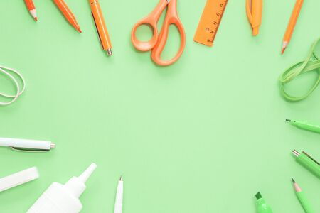 Assorted office and school orange and green white stationery on green background as border. Flat lay with copy space for back to school or education and craft concept Stok Fotoğraf