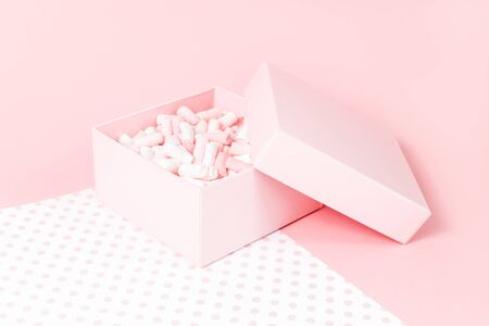 Feminine candy pink gift box with small marshmallows on pink and polka dot background. Passion, love and feelings St Valentines Mothers Womens Day celebration card monochromatic concept. copy space Фото со стока