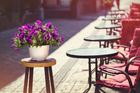 Row of empty cafe tables on old downtown street and a pot of flowers in front on bright summer day. Vacation travel with copy space Zdjęcie Seryjne - 129207586