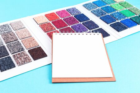 Multicolored carpet swatches catalogue book and notepad on blue desk background. Interior or refurbishment design with copy space