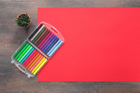 Assorted multicolored rainbow markers office or school set of stationery on red background. Flat lay with copy space. back to school or creative design education craft concept. Stok Fotoğraf