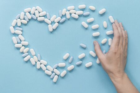 Background of white and blue tablets on blue table with pills shaping heart with female hand. Healthcare and medicine concept safe consumption with copy space Banque d'images