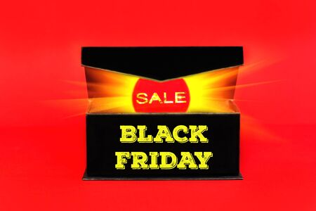 Red sale tag with glowing light out of black box on red background. Black friday banner with copy space Фото со стока