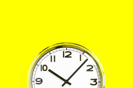 Part of analogue plain wall clock on trendy yellow background. Ten o'clock. Close up with copy space, time management or school concept and opening hours closing time