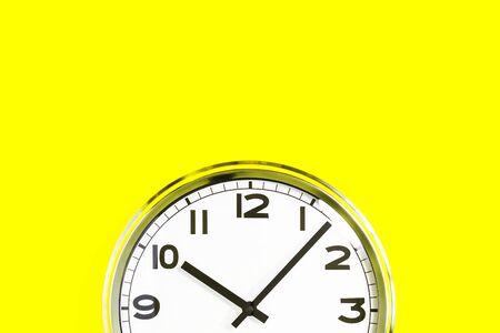 Teil der analogen einfachen Wanduhr auf trendigem gelbem Hintergrund. Zehn Uhr. Schließen Sie mit Kopienraum, Zeitmanagement oder Schulkonzept und Öffnungszeiten Schließzeit