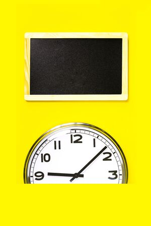 Part of analogue plain wall clock and black notice board on trendy yellow background. Nine oclock. Close up with copy space, time management or school concept and start time opening hours Imagens
