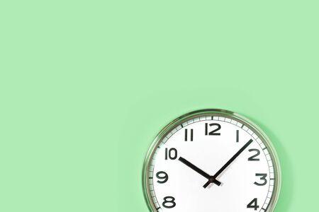 Onderdeel van analoge effen wandklok op trendy pastel mint achtergrond. tien uur. Close-up met kopieerruimte, tijdmanagementconcept en lunchtijd