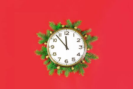 Merry Christmas or Happy New Year card with big wall clock at midnight showing five to twelve oclock. Christmas tree decor and lights on red background flat lay