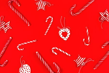 Merry Christmas or happy New Year pattern decor on red background with candy canes hearts and stars festive red and white monocromatic flat lay