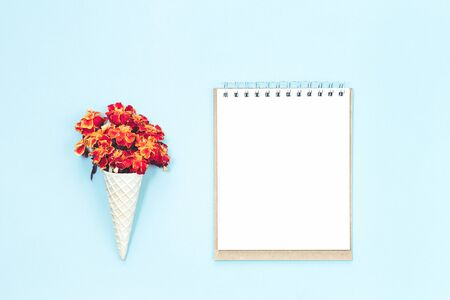 Blank notepad with orange autumn flowers in waffle cone on light blue desk. Autumn, fall, thanksgiving day concept. Flat lay, top view, copy space