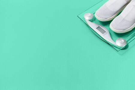 Lichtgewicht moderne textiel slip op sneakers schoenen met weegschaal op pastel biskaje groene achtergrond in plat lag met kopieerruimte. Gewichtsbeheersing en gezonde levensstijl sportconcept