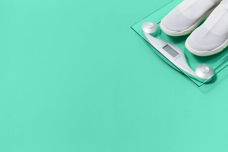 Lightweight modern textile slip on sneakers shoes with weighing scale on pastel biscay green background in flat lay with copy space. Weight management and healthy lifestyle sport concept 版權商用圖片