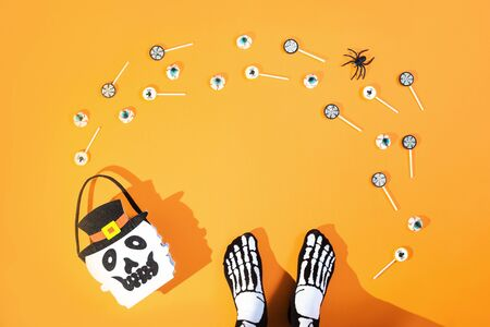 Happy Halloween candy bucket face of Jack O Lantern with lollypops with spiders and nets on orange background and bloody eyes sweets and sceleton feet. Flat lay trick or treat banner with copy space Stok Fotoğraf - 131390154